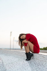 Spain, Barcelona, Montjuic, young woman wearing red dress sitting on a wall - AFVF01978