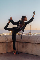 Spain, Barcelona, Montjuic, young woman doing yoga at dusk with city lights in background - AFVF01987