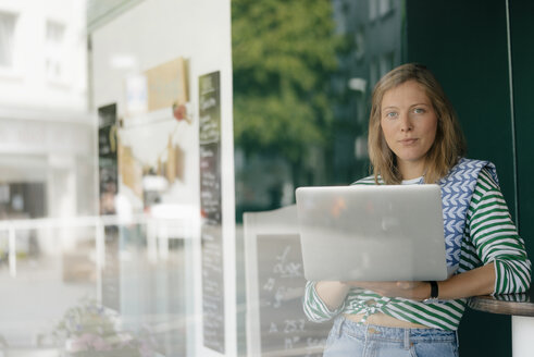 Portrait of young woman with laptop in a cafe - KNSF05288