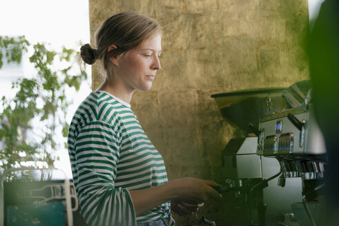 Young woman preparing coffee in a cafe - KNSF05297