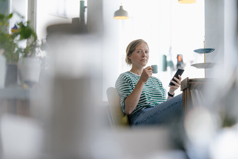 Portrait of young woman with cell phone and espresso in a cafe - KNSF05300