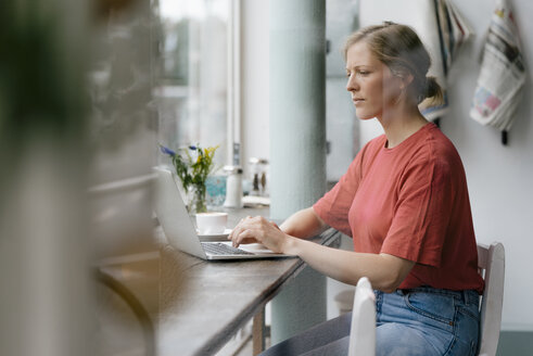 Young woman using laptop at the window in a cafe - KNSF05306