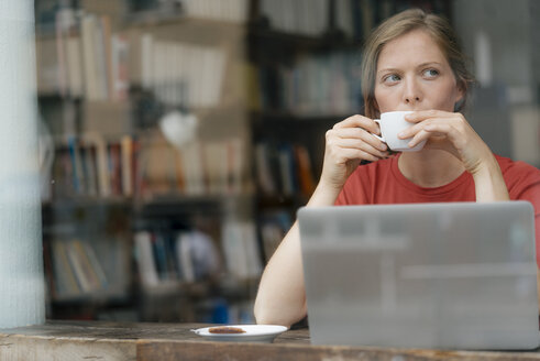 Young woman with cup of coffee and laptop in a cafe - KNSF05309