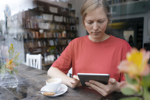 Young woman using tablet at the window in a cafe - KNSF05312