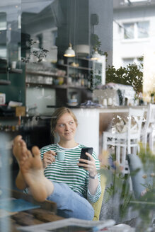 Smiling young woman with feet up holding cell phone and espresso cup in a cafe - KNSF05357