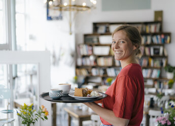 Portrait of smiling young woman serving coffee and cake in a cafe - KNSF05360