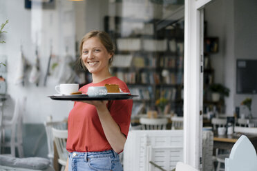 Portrait of smiling young woman serving coffee and cake in a cafe - KNSF05363