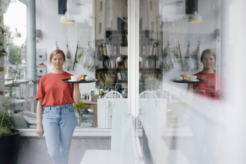 Portrait of young woman serving coffee and cake in a cafe - KNSF05366