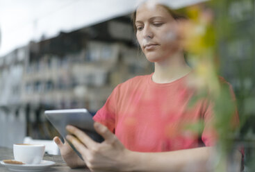 Young woman using tablet at the window in a cafe - KNSF05369