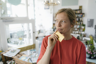 Young woman holding card in a cafe thinking - KNSF05384