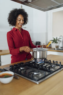 Woman standing in kitchen, preparing food - BOYF00957
