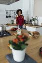 Woman drinking white wine in her kitchen, using smartphone - BOYF00975