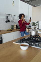 Woman drinking white wine in her kitchen, using smartphone - BOYF00978