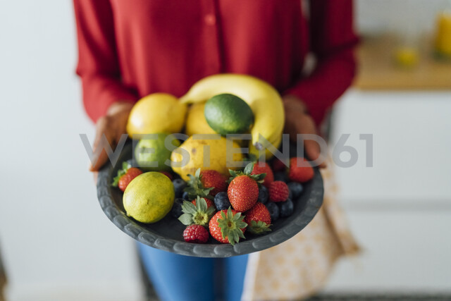 Woman holding plate with fruit - BOYF00996