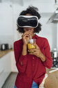 Woman standing in her kitchen, wearing VR goggles, drinking orange juice - BOYF00999