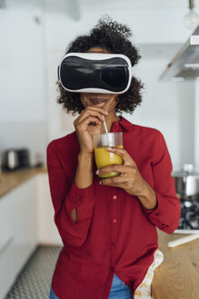 Woman standing in her kitchen, wearing VR goggles, drinking orange juice - BOYF00999