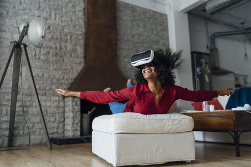 Woman lying on seating furniture, wearing VR goggles, pretending to fly - BOYF01005
