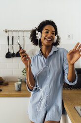 Woman dancing and listening music in the morning in her kitchen - BOYF01041