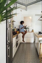 Woman sitting on worktop of her kitchen, using digital tablet in the morning - BOYF01047