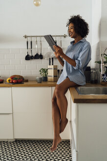 Woman sitting on worktop of her kitchen, using digital tablet in the morning - BOYF01053