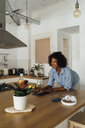 Woman using digital tablet and having a healthy breakfast in her kitchen - BOYF01056