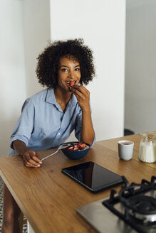 Woman using digital tablet and having a healthy breakfast in her kitchen - BOYF01059