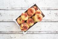 Doughnut peaches in wooden box on white wood - LVF07542