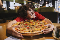 Happy woman holding pizza on wooden table while sitting in restaurant - CAVF54562