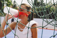 Young woman drinking water from bottle on soccer court seen through net - CAVF54565
