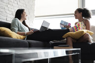 Happy lesbian couple planning vacation while sitting on sofa at home - CAVF54574