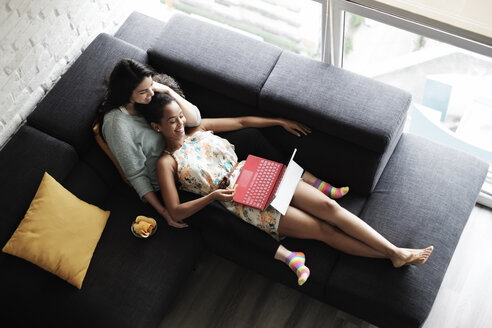 High angle view of lesbian couple watching video over laptop computer while relaxing on sofa in living room - CAVF54580