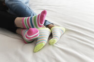 Low section of lesbian couple wearing colorful socks while relaxing on bed at home - CAVF54583
