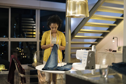 Female entrepreneur stitching jeans while standing by table in office - CAVF54592