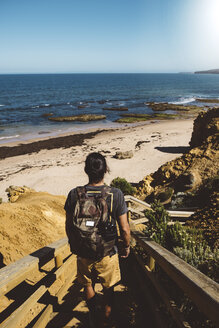Rear view of man with backpack standing on steps at beach against clear blue sky during sunny day - CAVF54607