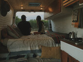 Couple relaxing on bed in motor home at forest - CAVF54622