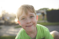 Portrait of cute smiling boy playing at playground during sunset - CAVF54628