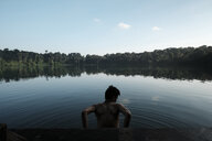 Rear view of shirtless man standing in lake against sky - CAVF54640