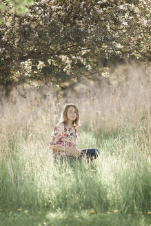 Portrait of girl sitting on grassy field under tree - CAVF54655