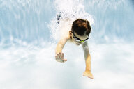 Shirtless boy wearing goggles while swimming in pool - CAVF54661