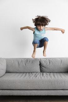 Playful boy with arms outstretched jumping on sofa against wall at home - CAVF54685