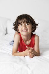 Cute happy boy with hands clasped looking away while relaxing on bed at home - CAVF54691