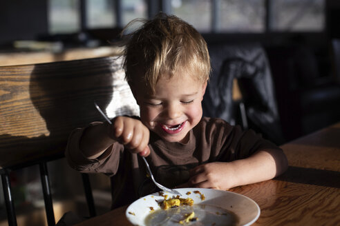 Close-up of cute happy boy eating food on wooden table while sitting at home - CAVF54694
