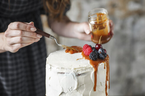 Midsection of woman icing cake with caramel and berry fruits at home - CAVF54697