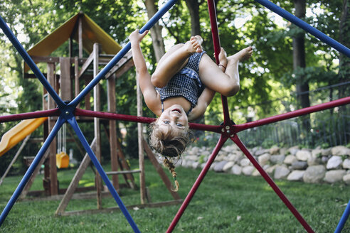 Portrait of cute smiling girl hanging upside down on jungle gym against trees at playground - CAVF54703