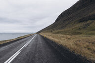 Empty road amidst mountain by sea against cloudy sky - CAVF54709