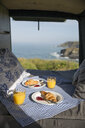 High angle view of breakfast on bed by window in motor home - CAVF54742