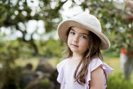 Portrait of cute girl wearing hat standing at park - CAVF54766