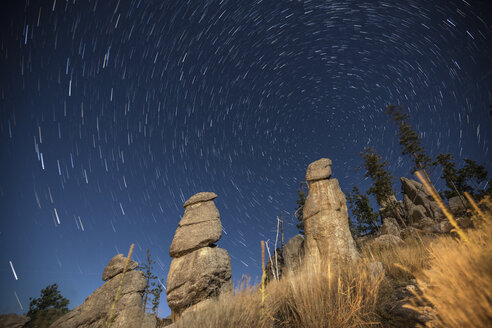 Low angle view of rock formations against star trails at night - CAVF54781