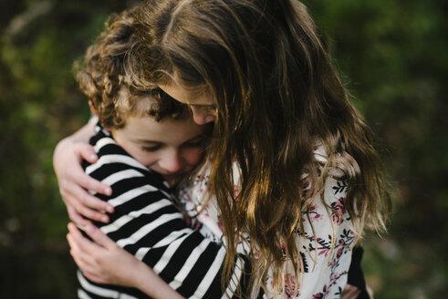 Close-up of loving siblings embracing at park - CAVF54796