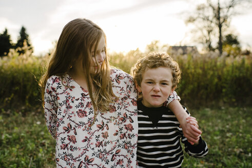 Portrait of brother making face while standing by sister at park - CAVF54802